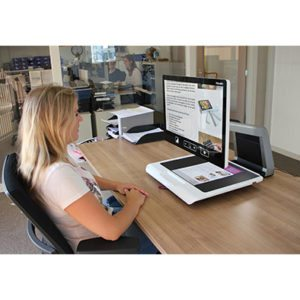 Woman using Acuity desktop magnifier.
